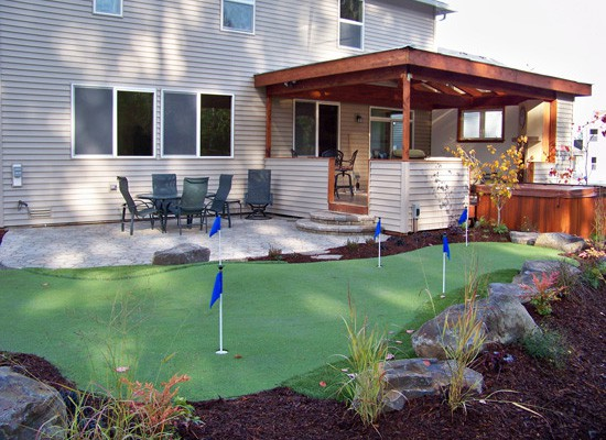 A paver patio and a synthetic putting green for fun and relaxation.